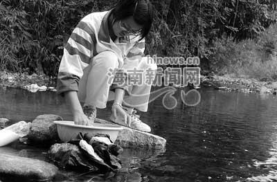 志愿者经常要到河边洗衣淘米.-访海南大学生志愿服务者 他们在西图片